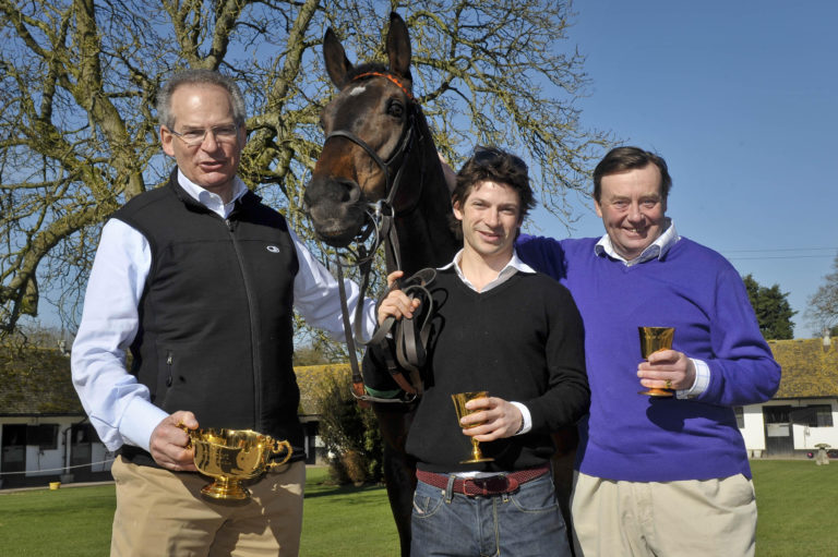 The Waley-Cohens and trainer Nicky Henderson (right) welcome Long Run home to Lambourn after his Gold Cup glory